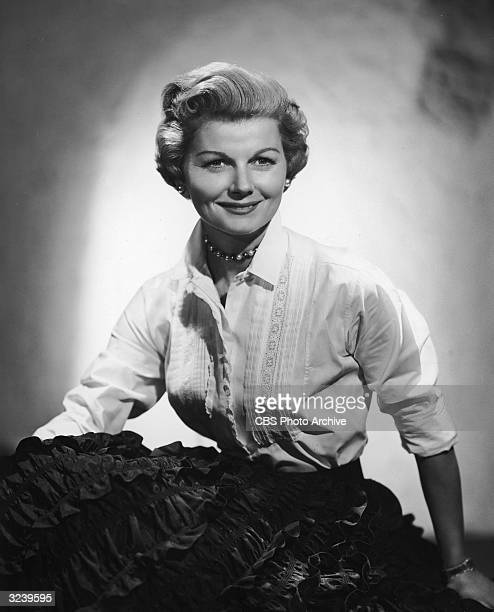 Studio portrait of American actor Barbara Billingsley seated and wearing a white blouse with lace stitching over a black ruffled skirt She played...