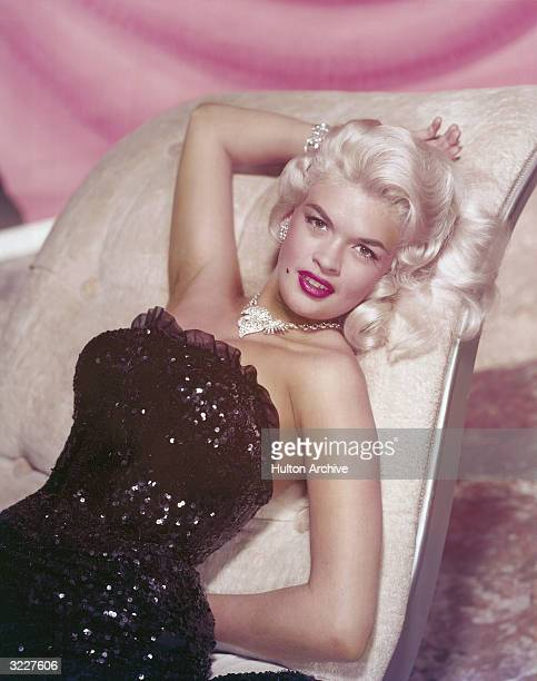 Studio portrait of American actor Jayne Mansfield reclining on chaise longue in a strapless sequined gown and diamond jewelry.