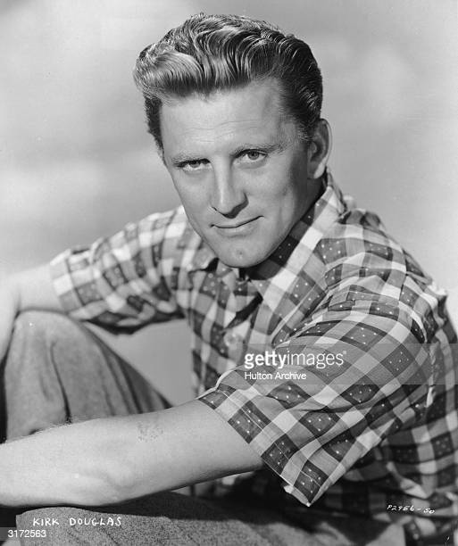 Studio portrait of American actor Kirk Douglas resting one arm on his knee and wearing a checkered short-sleeved shirt.