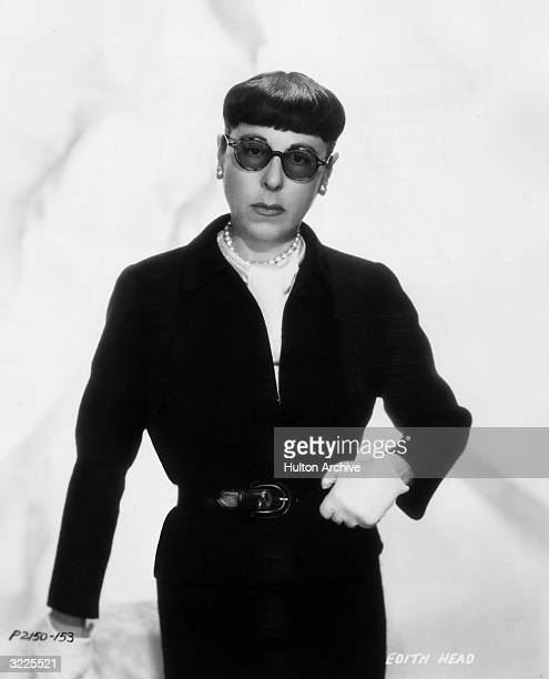 Studio portrait of American costume designer Edith Head head of the wardrobe department at Paramount Pictures wearing a black skirt suit white gloves...