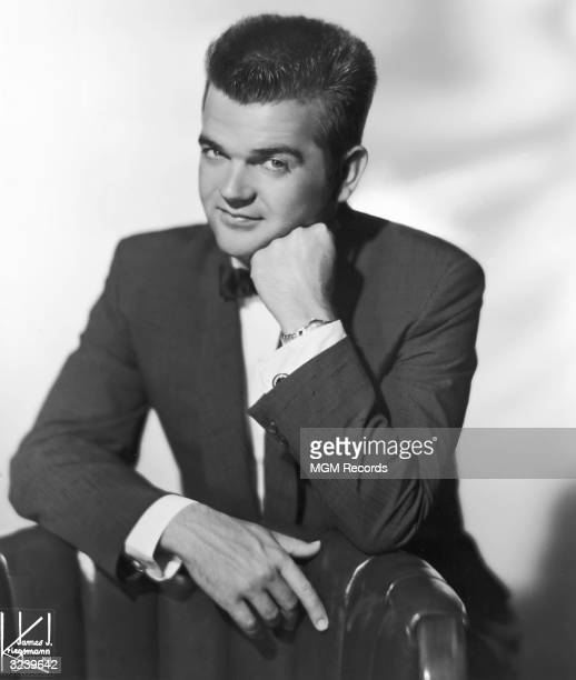 Studio portrait of American country and western singer and songwriter Conway Twitty wearing a jacket and bow tie and his face resting against his...