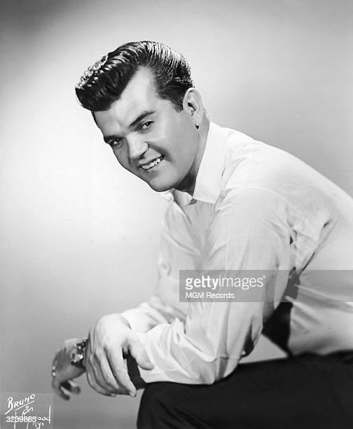 Studio portrait of American country and western singer and songwriter Conway Twitty , wearing a plain white shirt, looking over his shoulder while...
