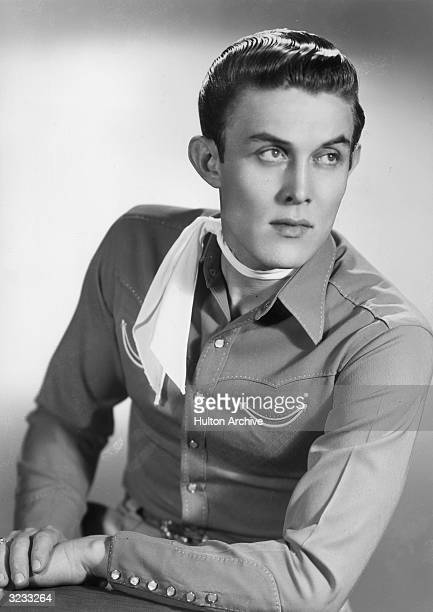 Studio portrait of American country singer and actor Jimmy Dean leaning on his elbow while wearing a western shirt and a scarf tied around his neck