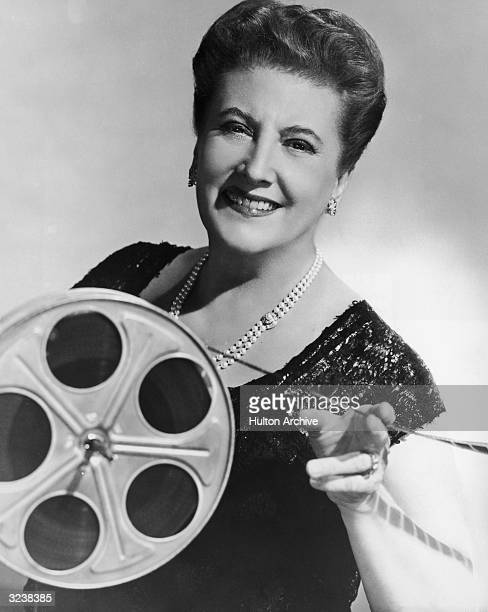 Studio portrait of American singer Helen Traubel smiling while holding a reel of film and film strip Traubel made her first film appearance in 1954...