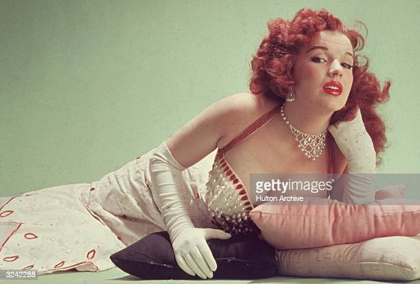 Studio portrait of Blaze Starr reclining on pillows on the floor wearing a redtrimmed white dress and white elbowlength gloves