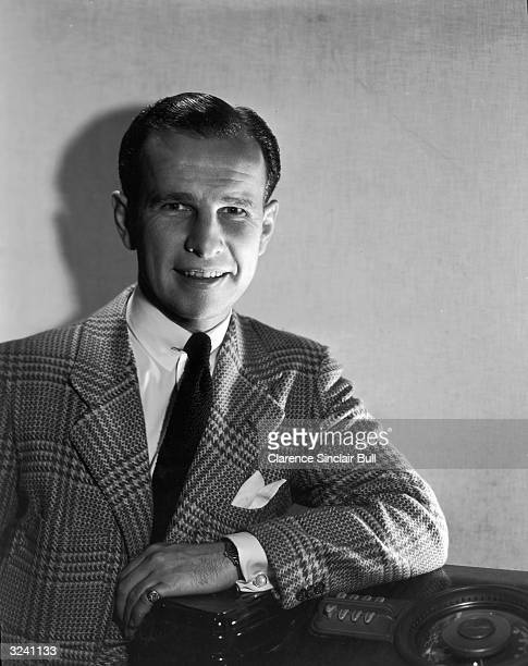 Studio portrait of Canadian-born actor Hume Cronyn resting his arm on a radio. He is wearing a tweed blazer with a shirt, tie, and cufflinks.
