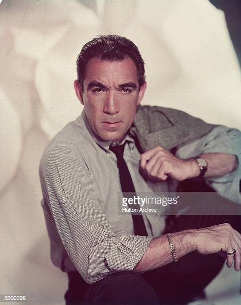 Studio portrait of Mexicanborn actor Anthony Quinn sitting and holding a sports coat over his shoulder He is wearing a shirt tie and silver bracelet