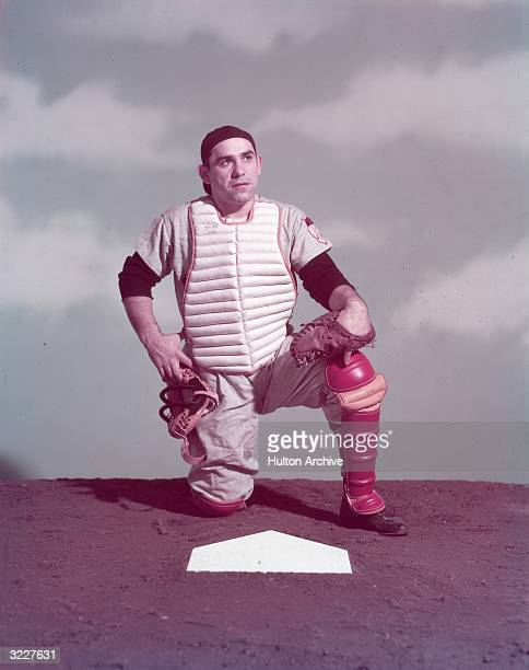 Studio portrait of New York Yankees catcher Yogi Berra kneeling in uniform with his mask off behind home plate