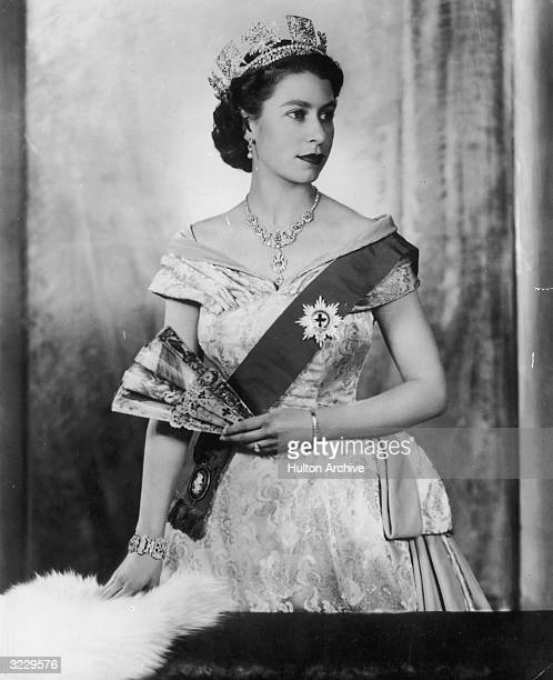 Studio portrait of Queen Elizabeth II holding a fan while wearing a brocade dress She is also wearing a sash and the star of the Order of the Garter...