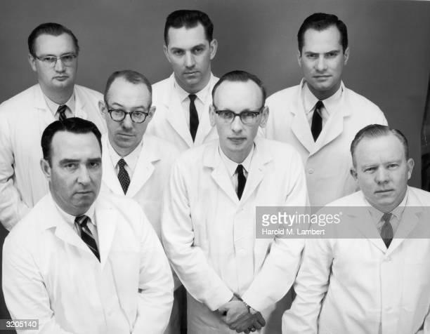 Studio portrait of seven men in white lab coats. Three of the men wear horn-rimmed glasses.