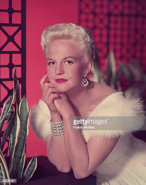 Studio portrait of singer Peggy Lee wearing a fur trimmed white gown and diamond earrings leaning on a potted plant