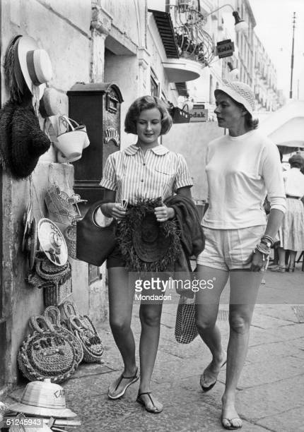Circa 1955, Swedish-born actor Ingrid Bergman, right, with her daughter Pia Lindstrom while walking down a market street in Capri, Italy, 1950s. The...