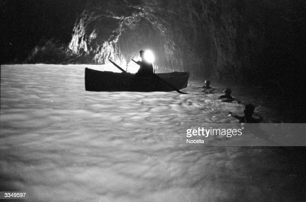 Swimmers and visitors by boat are silhouetted against the eery blue glow of the water in the Blue Grotto at Capri.