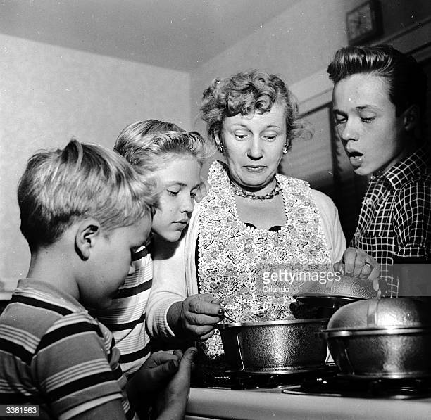 Television stars Ken Ronnie and Glenn Walken watch as their mother Rosalie prepares supper at their home in Bayside Long Island