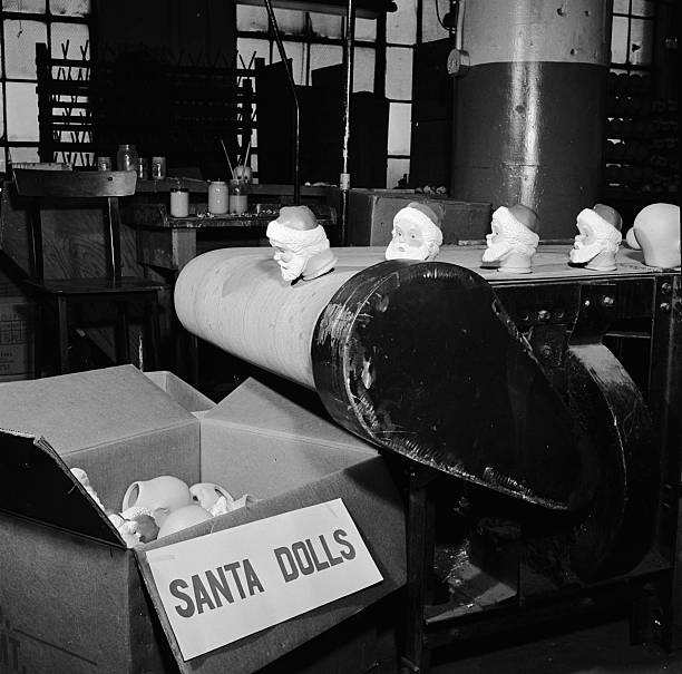 The heads of Santa Claus dolls fall from a conveyor...