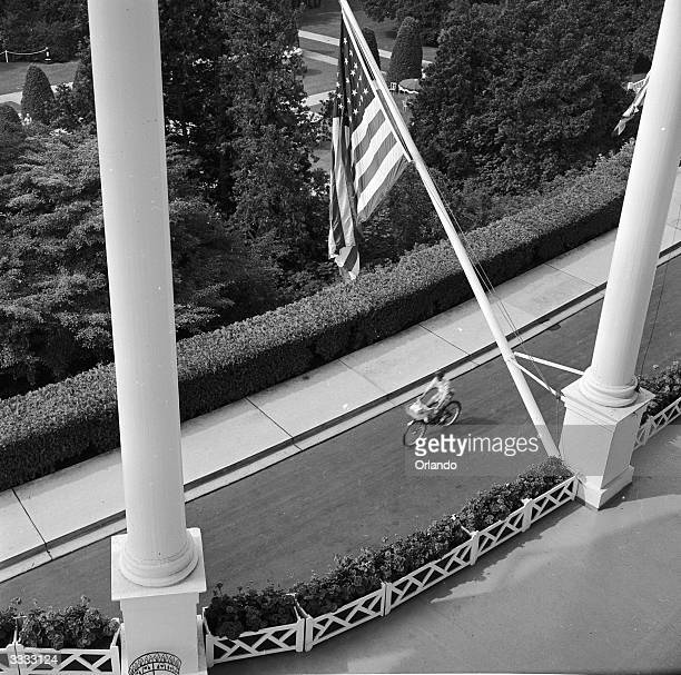The pillars of a large porch with an American flag draped between them at the Grand Hotel on Mackinac Island Michigan