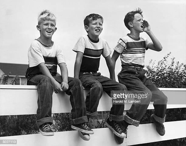 Three freckled boys sit on top of a white fence wearing striped shirts and jeans One of the boys shouts with his hand cupped to his mouth