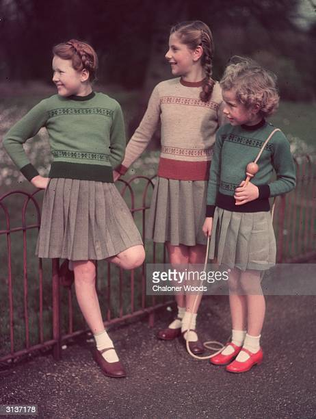 Three little girls wearing jumpers with a matching pattern identical pleated skirts and ankle socks The littlest girl carries a skipping rope over...