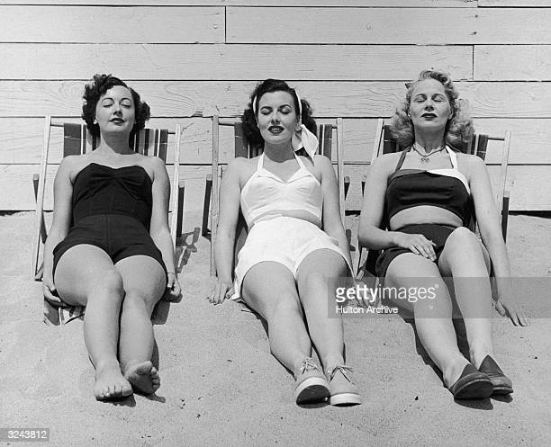 Three women in bathing suits sunbathe against a wall on a beach early 1950s