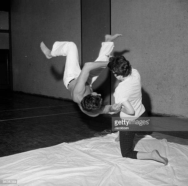 Toni Carroll breaks a choke hold by gripping her attacker's arms during a judo demonstration at Al Roon's Health Club