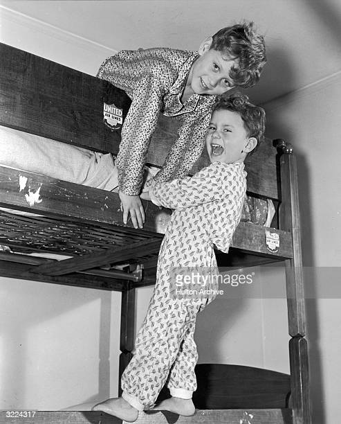 Two brothers smile as they play on their bunk bed wearing pajamas One boy leans over the edge of the top bunk as the other boy stands on the side of...