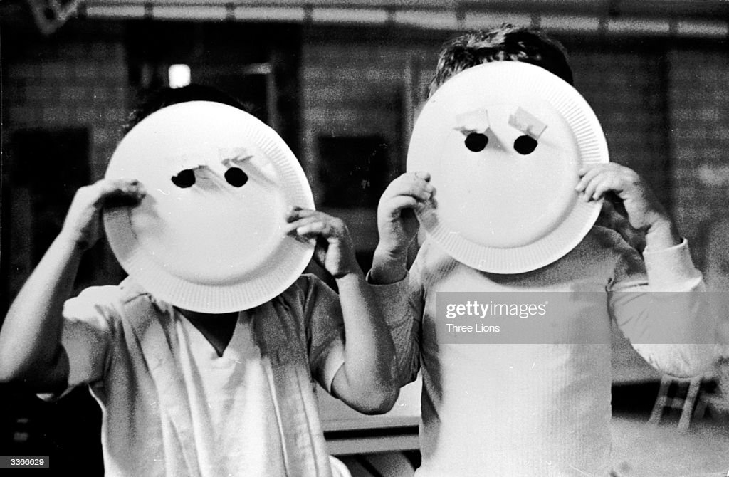Two children holding up paper plate masks with holes for eyes.
