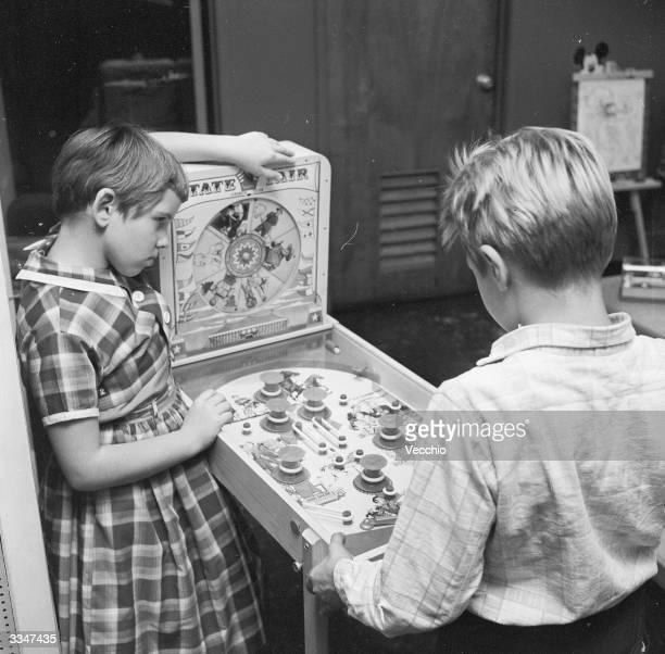 Two children playing a mini pinball machine