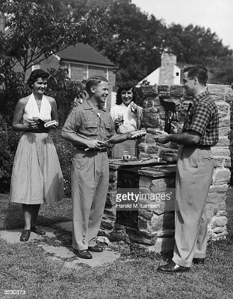 Two couples have beer and hot dogs outdoors at a stone barbecue grill.
