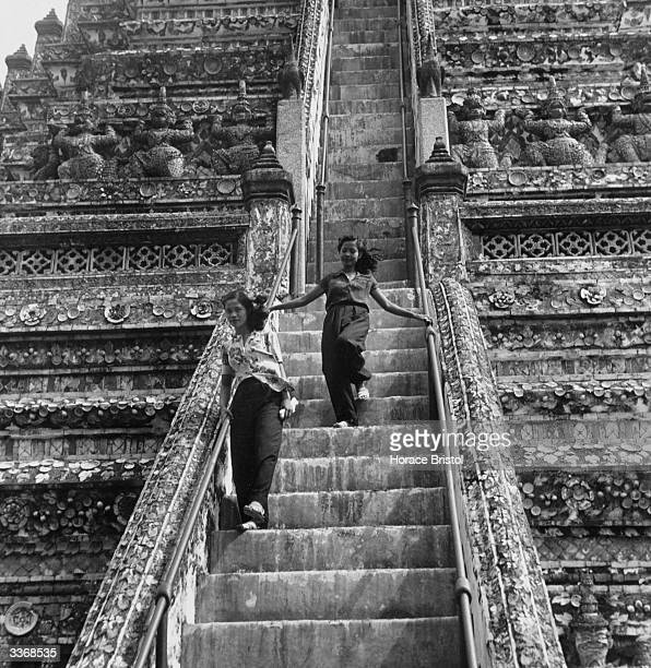 Two girls walking down the steep steps of the Wat Arun one of the most ornate of Bangkok's pagoda temples It was built by King Phra Chao Tak and was...