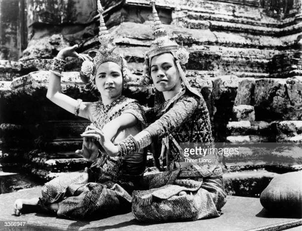 Two of the Royal dancers of Cambodia wearing colourful brocade costumes and diamond encrusted head dresses striking a pose from an ancient...