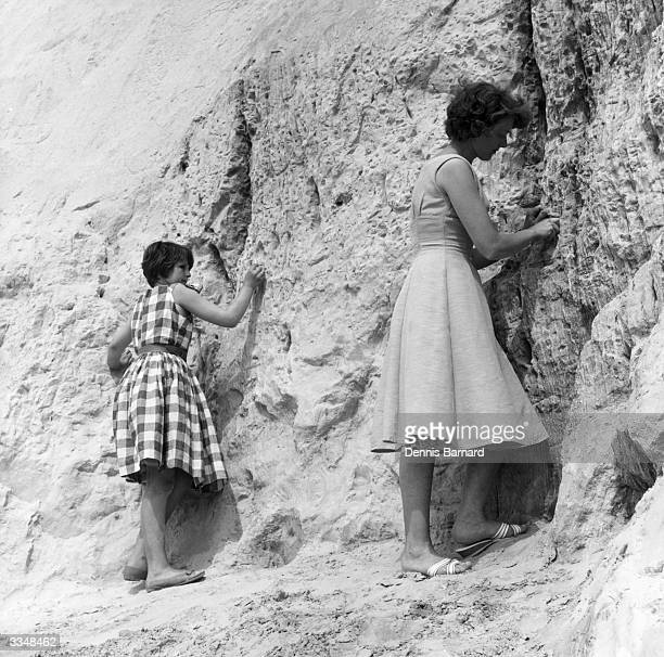 Two tourists collecting the sand at Alum Bay in the Isle Of Wight from the cliffs which have many different coloured layers.