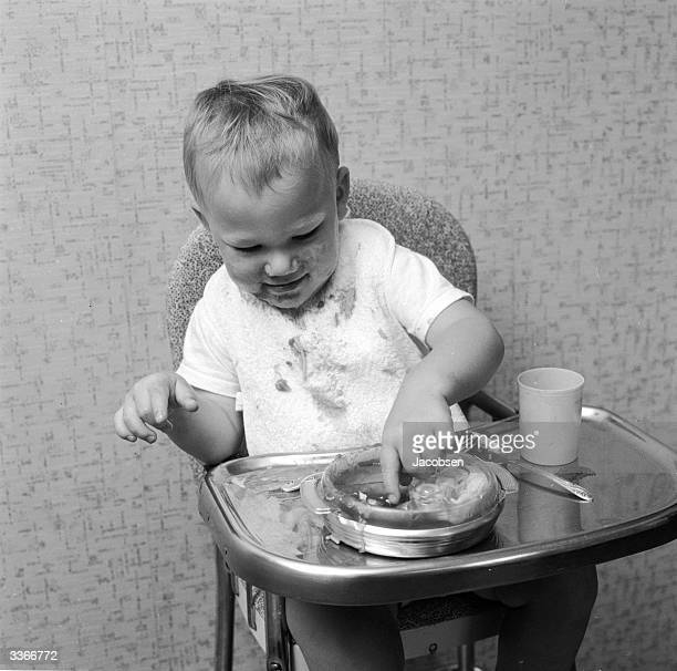 Two year old Erroll Isenberg is amused by the slippery spaghetti pieces in his dish which squish from under his fingers