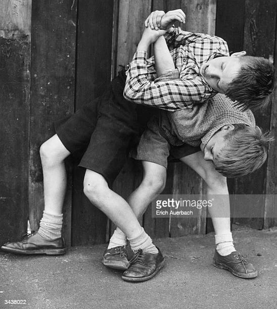 Two young boys wrestling in fun one has the other in an armlock