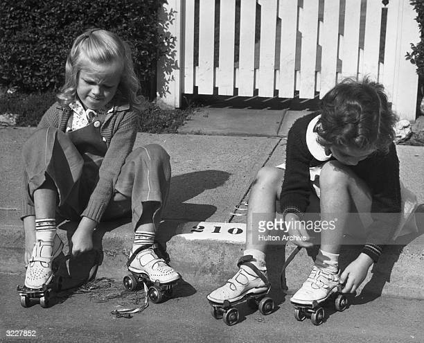 Two young girls sit outdoors on a curb putting on their roller skates