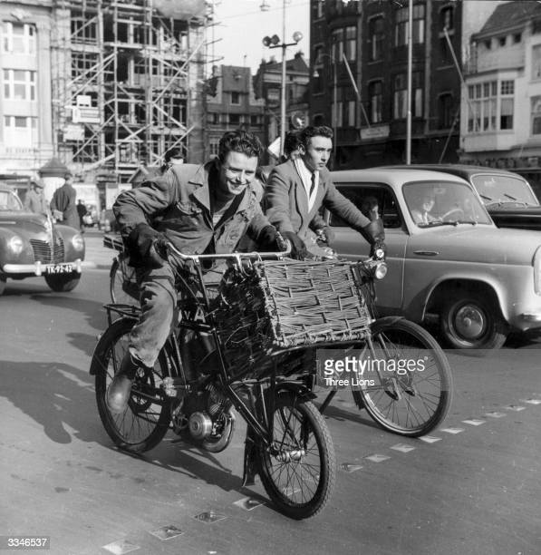 Two young men cycling amongst traffic in Holland one on a bicycle with a motor attached and a large basket at the front