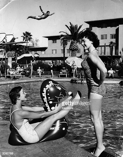 Two young women enjoying themselves by the pool at a Las Vegas holiday resort while a man performs a spectacularly high dive in the background