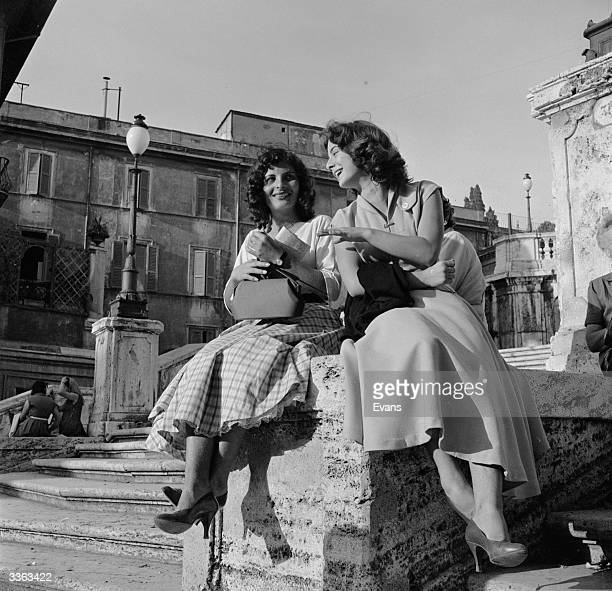 Two young women share a joke during their lunch hour in Rome