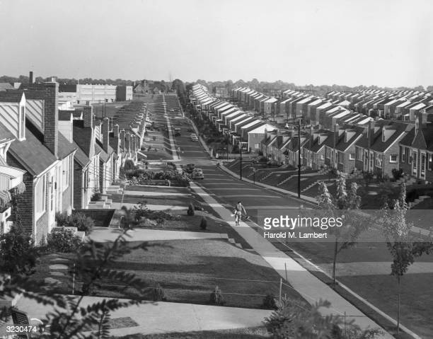 View of a long sloping suburban street flanked by rows of identical tract houses A paperboy walks down the sidewalk