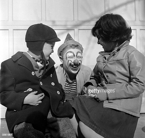 Young clown Ronnie Walken later film star Christopher Walken poses with two children on his knee during an interlude in the backyard where he has...