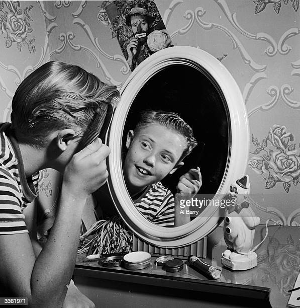 Young clown Ronnie Walken later film star Christopher Walken combing his hair in front of a mirror