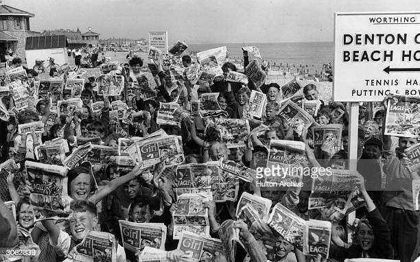 Young holidaymakers in Worthing Sussex waving copies of the Eagle and Girl comics