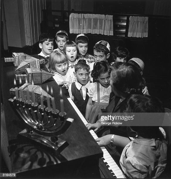 Young Jewish children gather around the piano to perform songs during the Chanukah celebrations A spin of the dreidl lying on top of the piano is...