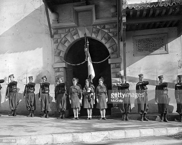 Zouave guards flank a French Women's Army parade outside the wall of an historic casbah fortress in Algiers