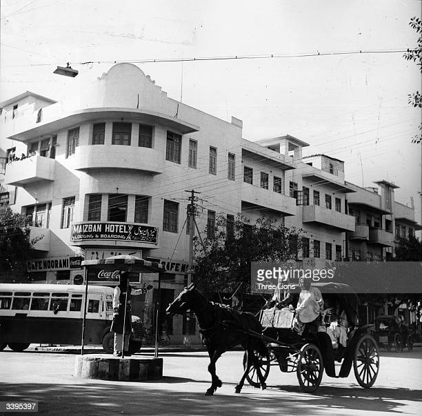 A horse and cart crossing a junction controlled by a policeman on the Bunder Road in Karachi Pakistan