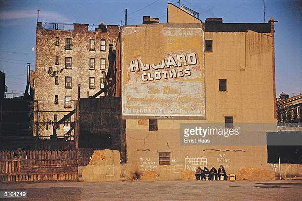 A row of men sit under graffitti and an old poster on an ochre coloured plastered wall of a tenement buildings in a poor quarter Of New York