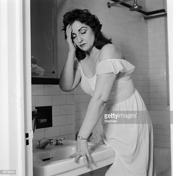 A woman still dressed in her nightgown makes a distressed morning visit to her bathroom feeling unwell sufferring from the effects of a hangover