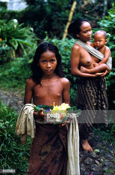 A young barebreasted Balinese girl carries a leaf filled with flowers In the background her mother carries a baby in a sling