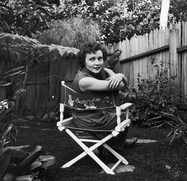 American actor Betty White sits in a canvas chair with her name written on the back, looking over her shoulder in a backyard garden.