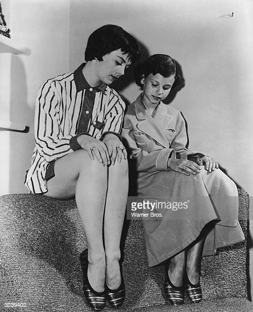 American actor Natalie Wood and her sister Lana Lisa Wood wear matching Honeybugs slippers while sitting together on the set of director John Ford's...