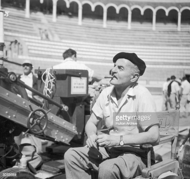 American film executive producer and screenwriter Darryl F Zanuck smokes a cigar from his director's chair in a bull ring on the set of director...